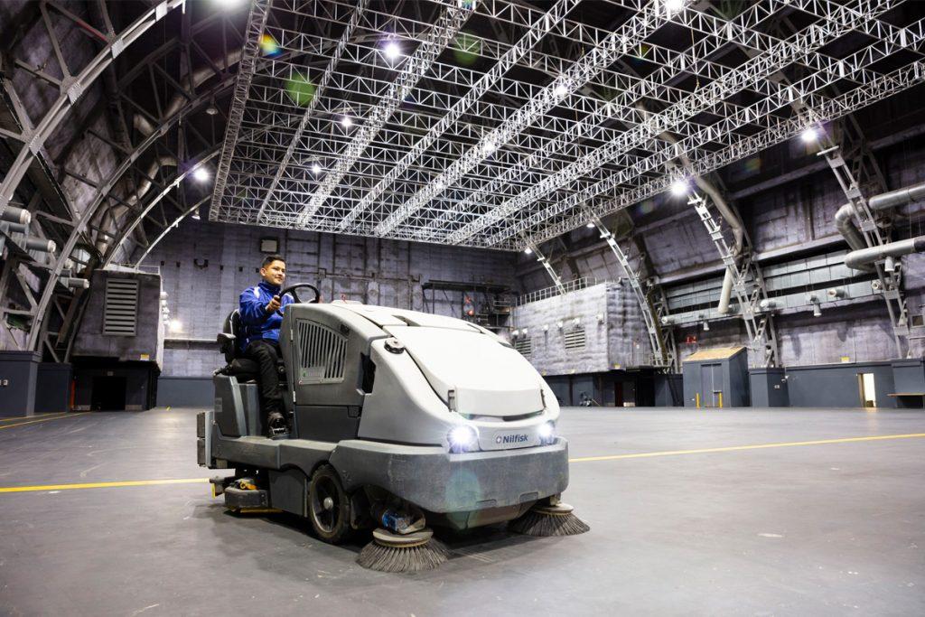 A Quayclean team member driving a ride-on sweeper in soundstage at Fox Studios NSW