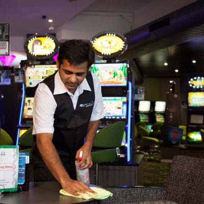 Quayclean team member wiping and disinfecting table in gaming room