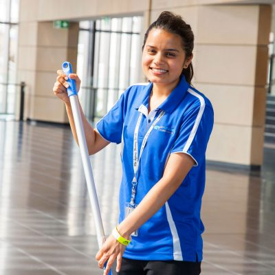Quayclean staff member mopping floor and smiling
