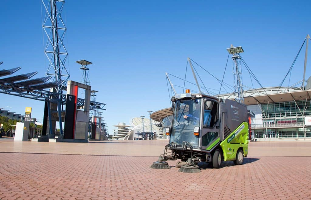 Quayclean team member in street sweeper outside stadium