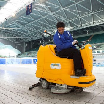A Quayclean team member using a ride-on tile scrubbing machine to clean sports and aquatic centre
