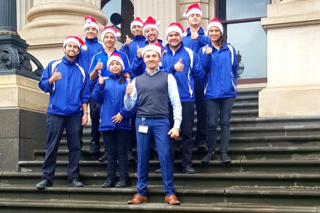 The Quayclean team wearing santa hats giving the thumbs up on the stairs of Parliament of Victoria