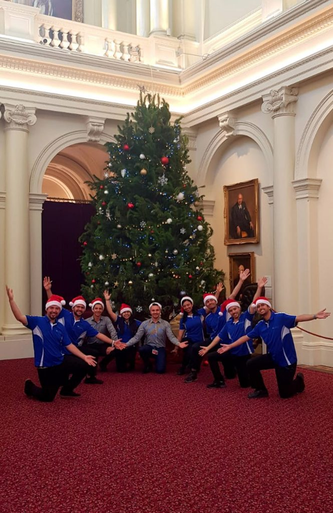 The Quayclean team wearing santa hats kneeling in front of a Christmas tree in Parliament House