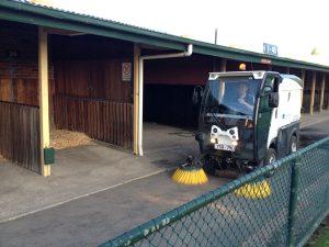 Quayclean team member in street sweeper outside stables